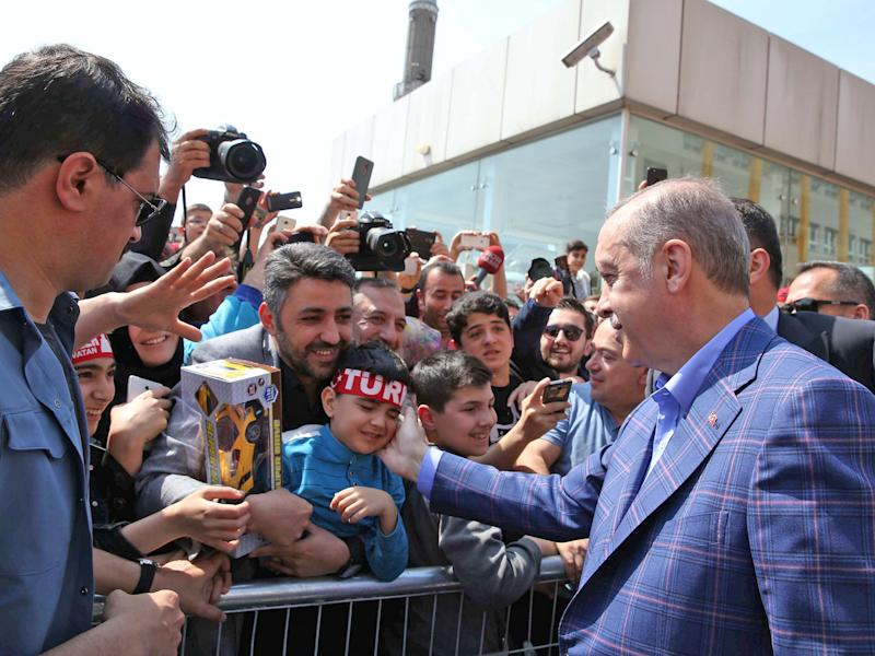 President Erdogan greets supporters outside a polling station. A 'yes' vote would make him immensely powerful: REUTERS
