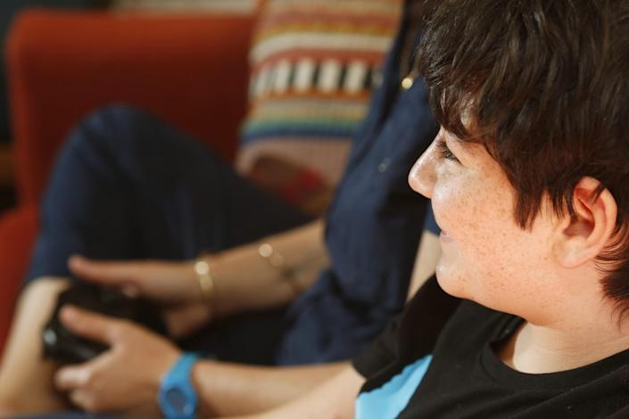 A tween boy smiles while playing video games with his mom.
