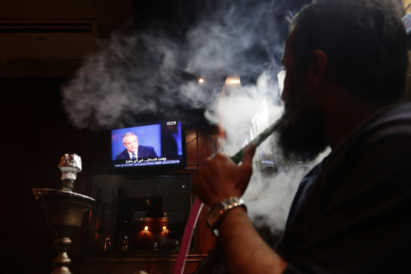 """A man smokes a water pipe as he watches Jon Stewart on a TV screen at a coffee shop, in Cairo, Egypt, Saturday, June 22, 2013. Jon Stewart has appeared on Egypt's top satirical TV program, modeled after his own program """"The Daily Show."""" Stewart was brought to the set wearing a black hood and introduced by host Bassem Youssef as a captured foreign spy. (AP Photo/Hassan Ammar)"""