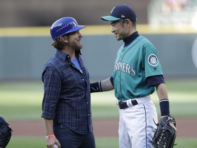 Eddie Vedder, left, of the rock band Pearl Jam, talks with Ichiro Suzuki, special assistant to the chairman, Friday, July 20, 2018, after Vedder threw out the first pitch of a baseball game between the Mariners and the Chicago White Sox at Safeco Field in Seattle to Suzuki. Pearl Jam is scheduled to play two concerts in August at the ballpark. (AP Photo/Ted S. Warren)