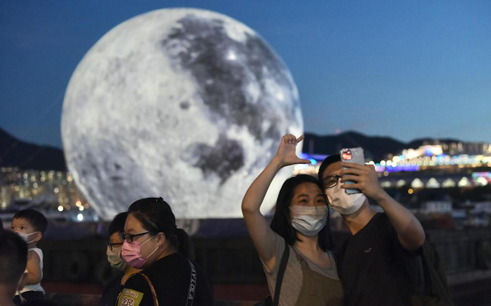 People visit an illuminated art installation of the moon to celebrate the Mid-Autumn Festival at Kwun Tong Promenade in Hong Kong - Getty