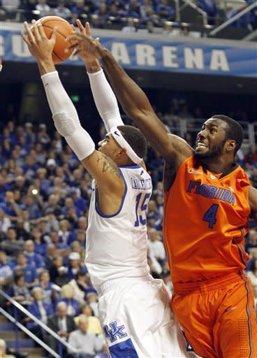 Kentucky's Willie Cauley-Stein, left, shoots as Florida's Patric Young defends during the first half of an NCAA college basketball game at Rupp Arena in Lexington, Ky., Saturday, March 9, 2013. (AP Photo/James Crisp)