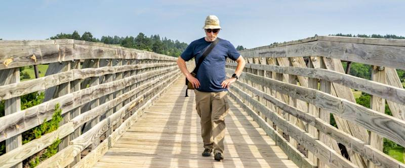 senior male walking on old railroad trestle acroos Niobrara River , now a multi-use recreational Cowboy Trail in northern Nebraska