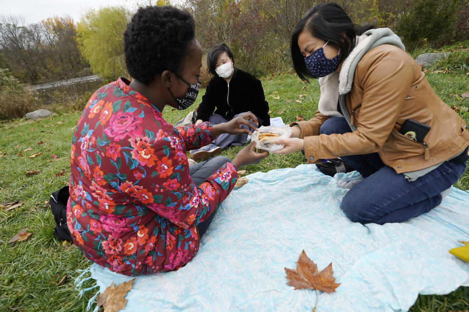 From left, urban planners Daphne Lundi, Gloria Lau and Giovania Tiarachristie share Caribbean currant rolls from a nearby bakery as they gather near a waterway, Sunday, Nov. 15, 2020, in Prospect Park in the Brooklyn borough of New York. (AP Photo/Kathy Willens)
