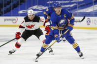 Buffalo Sabres forward Jack Eichel (9) carries the puck past New Jersey Devils forward Yegor Sharangovich (17) during the second period of an NHL hockey game Saturday, Jan. 30, 2021, in Buffalo, N.Y. (AP Photo/Jeffrey T. Barnes)