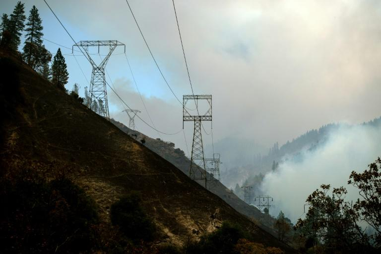 Power lines are seen on November 11, 2018 against a smoky landscape near Pulga, California, east of Paradise, California