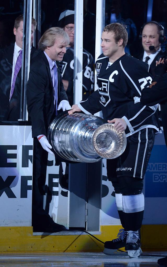 LOS ANGELES, CA - JANUARY 19: Dustin Brown #23 of the Los Angeles Kings takes the Stanley Cup from Phil Pritchard of the Hockey Hall of Fame before the NHL season opening game between the Chicago Blackhawks and the Los Angeles Kings at Staples Center on January 19, 2013 in Los Angeles, California. (Photo by Harry How/Getty Images)