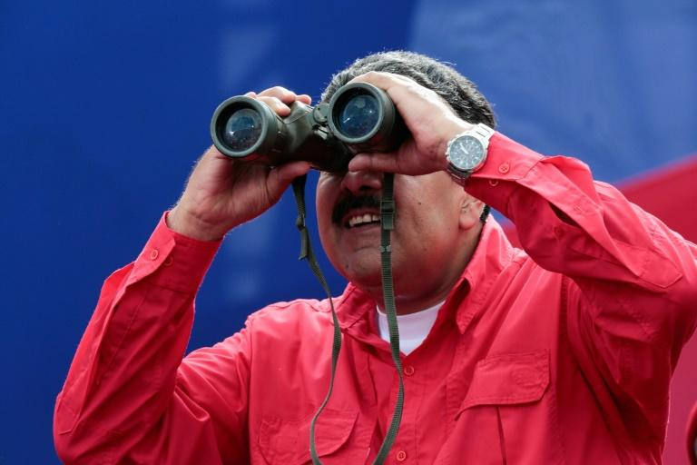 Venezuelan presidential office showing President Nicolas Maduro watching with binoculars during a rally in Caracas on April 19, 2017