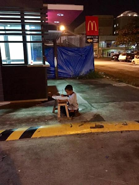 Photo taken on June 23, 2015 by student Joyce Torrefranca shows homeless nine-year-old boy Daniel Cabrera doing his homework on a wooden stool outside a McDonald's in Mandaue, central Philippines (AFP Photo/Joyce Torrefranca)