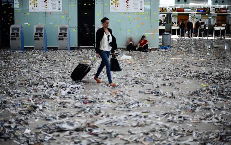 A passenger walk among rubbish and paper during a strike by the cleaning staff against budget cuts at Barcelona's airport in Barcelona, Spain, Wednesday, May 30, 2012. (AP Photo/Manu Fernandez)