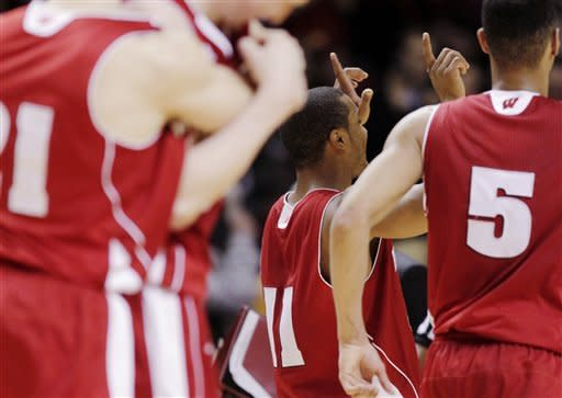Wisconsin's Jordan Taylor (11) celebrates with teammates after Wisconsin defeated Minnesota 68-61 in overtime in an NCAA college basketball game Thursday, Feb. 9, 2012, in Minneapolis. (AP Photo/Genevieve Ross)