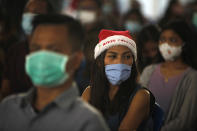 Indonesian Catholics wearing face masks to protect against coronavirus, attend a Christmas mass service at a church in Bali, Indonesia on Thursday, Dec. 24, 2020. (AP Photo/Firdia Lisnawati)