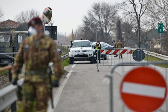 Italian soldiers patrol by a check-point at the entrance of the small town of Vo Euganeo, situated in the red zone of the COVID-19 the novel coronavirus outbreak, northern Italy, on February 24, 2020.