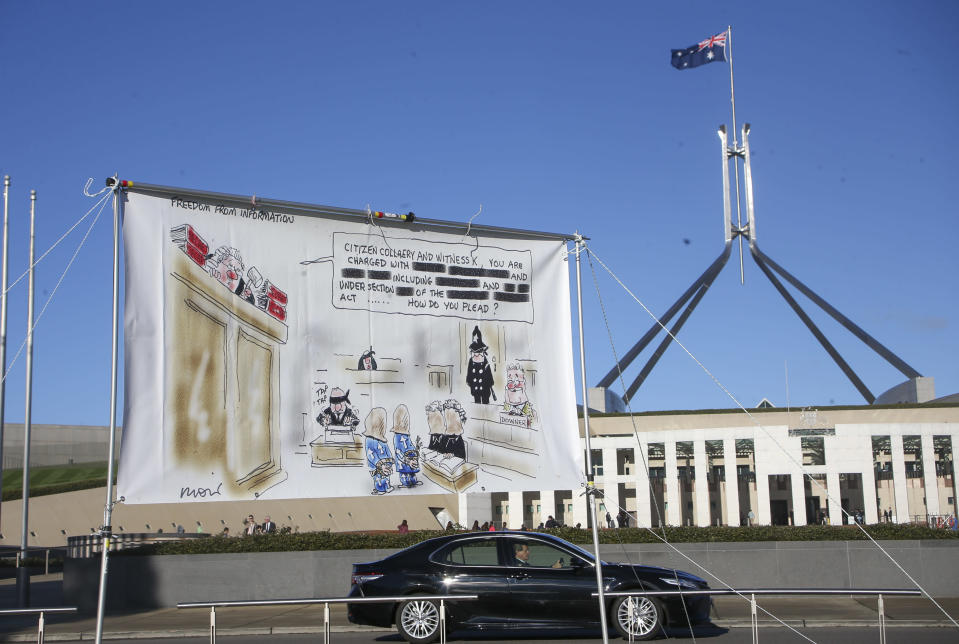A large banner hangs outside Parliament House in Canberra, Australia, Thursday, June 17, 2021 during a protest against the prosecution of lawyer Bernard Collaery whose picture is on the demonstrator's shirt. Critics of the secret prosecutions of a former Australian spy and his lawyer argue they are another example of a government concealing political embarrassment under the guise of national security. (AP Photo/Rod McGuirk)