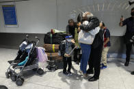Members of the Mogul family, a father hugs his daughter, who arrived with her son, bottom left, on a flight from Charlotte, North Carolina, in the U.S., at Terminal 5 of Heathrow Airport in London, Monday, Aug. 2, 2021. Travelers fully vaccinated against coronavirus from the United States and much of Europe were able to enter Britain without quarantining starting today, a move welcomed by Britain's ailing travel industry. (AP Photo/Matt Dunham)