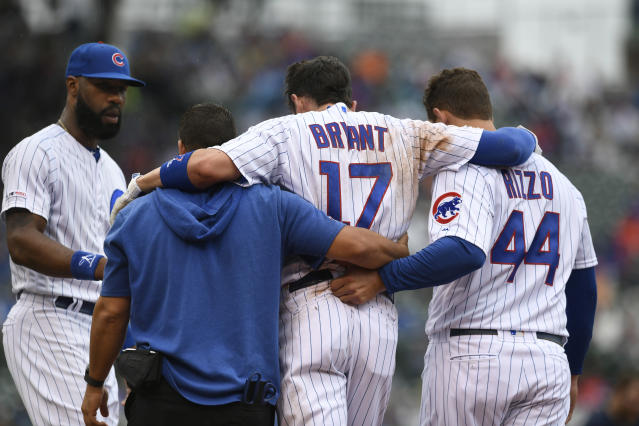 Chicago Cubs' Kris Bryant (17) is helped off the field by teammate Anthony Rizzo (44) and a trainer after getting hurt sliding into first base while teammate Jason Heyward left, looks on during the third inning of a baseball game against the St. Louis Cardinals, Sunday, Sept. 22, 2019, in Chicago. (AP Photo/Paul Beaty)