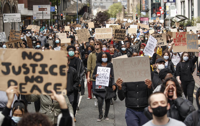 People take part in a Black Lives Matter protest rally in Manchester, England, Sunday, June 7, 2020, in response to the recent killing of George Floyd by police officers in Minneapolis, USA, that has led to protests in many countries and across the US. (Danny Lawson/PA via AP)