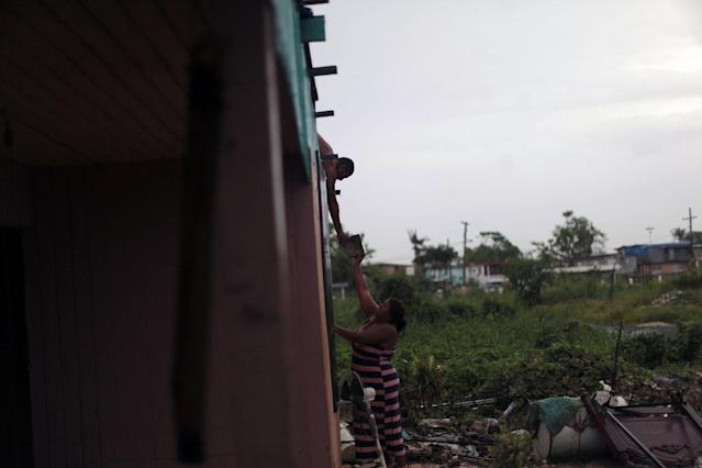 <p>A neighbour helps a woman to fix the roof of her home, after the island was hit by Hurricane Maria in Toa Baja, Puerto Rico, Oct. 16, 2017. (Photo: Alvin Baez/Reuters) </p>