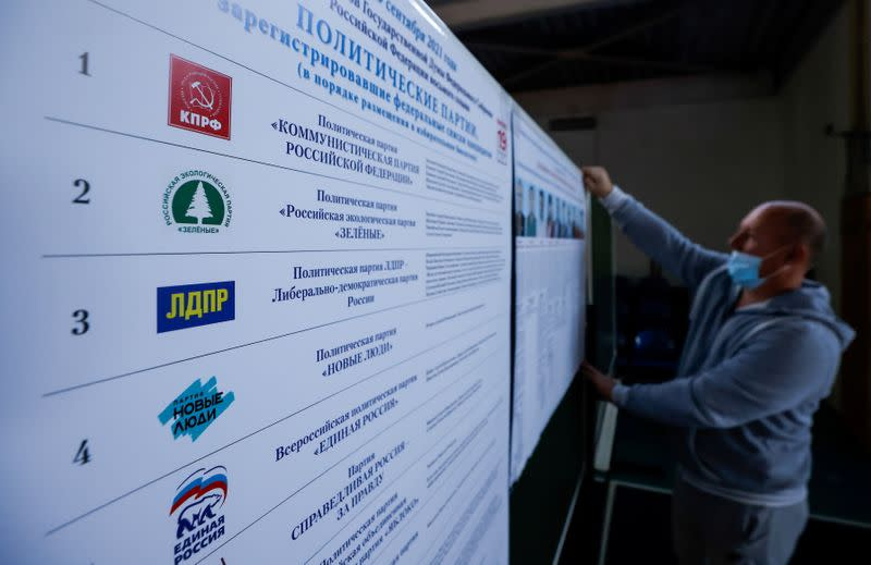 FILE PHOTO: A member of local election committee attaches a poster with pictures of candidates at a polling station ahead of parliamentary elections in the village of Ivolginsk