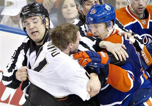 Anaheim Ducks Saku Koivu (left) and Edmonton Oilers Nick Schultz get pulled apart during third period NHL hockey action in Edmonton, Alberta Sunday April 21, 2013. (AP Photo/ The Canadian Press, Janson Franson)