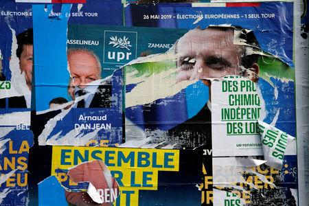 Torn and overlapping official posters of candidates for the 2019 European parliament elections including a poster of French President Emmanuel Macron as the cover for the Renaissance (Renewal) list, are seen in Cambrai, France, May 27, 2019. REUTERS/Pascal Rossignol