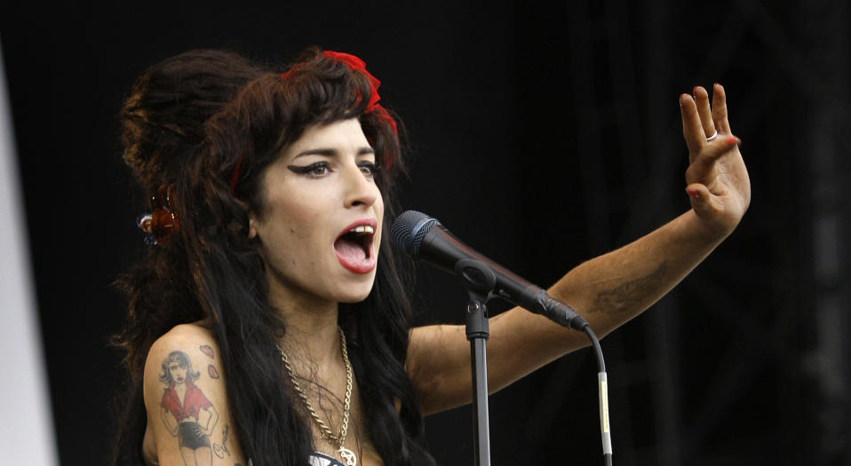 "FILE - In this Aug. 17, 2008 file photo, British singer Amy Winehouse performs at the V Festival in Chelmsford, Essex. The first-ever Amy Winehouse exhibit in the U.S. will debut at the Grammy Museum in Los Angeles next month. The Recording Academy told The Associated Press on Thursday, Dec. 19, 2019, that the late British singer's popular outfits - including her halter dress worn at her final stage performance in Belgrade in 2011 - never-before-seen handwritten lyrics and home video, journal entries and more from her family's personal archive will make up ""Beyond Black - The Style of Amy Winehouse."