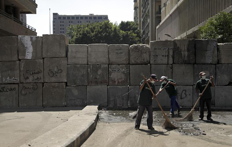 Egyptian street cleaners clean up the area around the U.S. embassy in Cairo, Egypt, Saturday, Sept. 15, 2012 after days of protests near the U.S. embassy over a film insulting Prophet Muhammad.(AP Photo/Khalil Hamra)