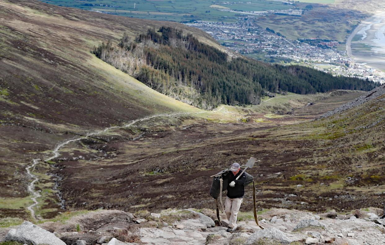 National Trust mountain ranger James Fisher constructing the final stages of the stone path on Slieve Donard in Newcastle, Co Down (Niall Carson/PA)