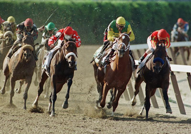 FILE - In this June 5, 1999, file photo, Lemon Drop Kid, left, with Jose Santos up; Stephen Got Even, second from left, with Shane Sellars up; Charismatic, second from right, with Chris Antley up; and Silverbulletday, with Jerry Bailey up, right, come around the fourth turn during the Belmont Stakes horse race at Belmont Park in Elmont, N.Y. Lemon Drop Kid won the race. (AP Photo/John Dunn, File)