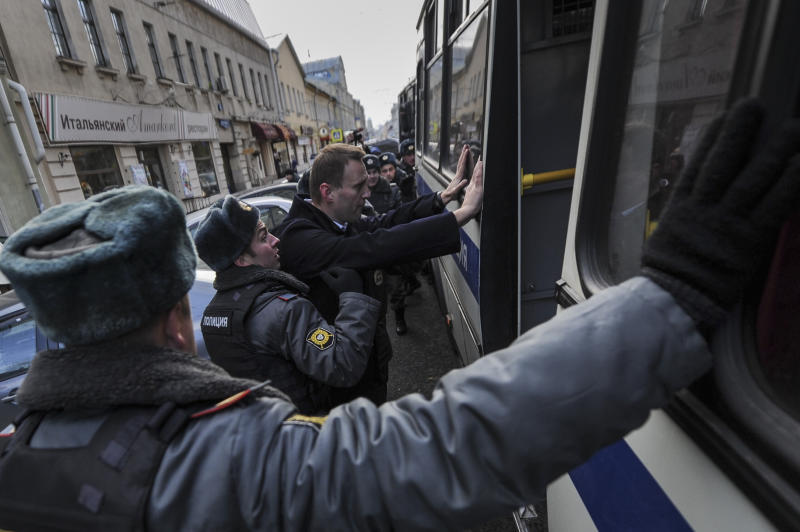 Opposition leader Alexei Navalny is searched by a police officer after being detained in Moscow, Saturday Oct. 27, 2012. Russian opposition leaders have been detained while protesting against torture which they believe was applied to their fellow activist. (AP Photo/Sergey Ponomarev)