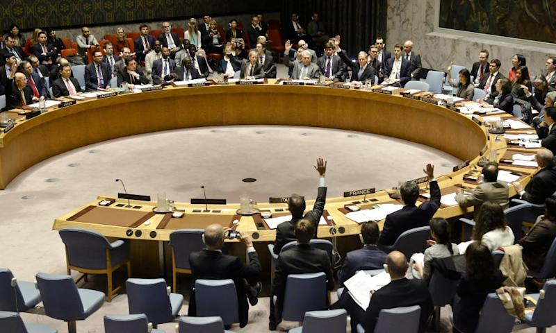 UN security council members show hands for a vote on a resolution condemning Syria's use of chemical weapons.