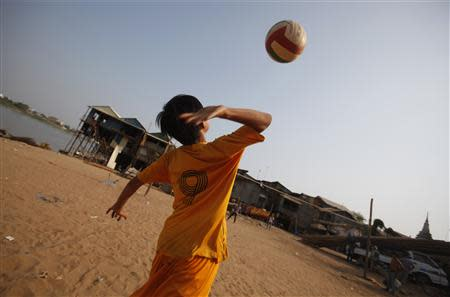 A Vietnamese boy plays volleyball with his friend near their house on the banks of the Mekong river in Phnom Penh March 11, 2014. REUTERS/Samrang Pring