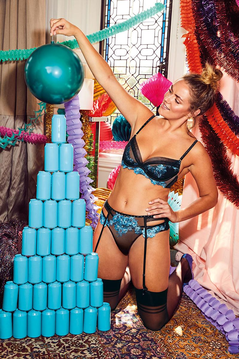 A photo of Katie Muirhead wearing a black and blue matching bra, underwear and suspender in Bras N Things' holiday campaign.