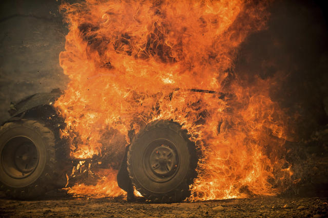 <p>Flames from a wildfire consume an all-terrain vehicle near Oroville, Calif., on Saturday, July 8, 2017. Residents were ordered to evacuate from several roads in the rural area as flames climbed tall trees. The California Department of Forestry and Fire Protection reported that several residents and one firefighter suffered minor injuries. (AP Photo/Noah Berger) </p>