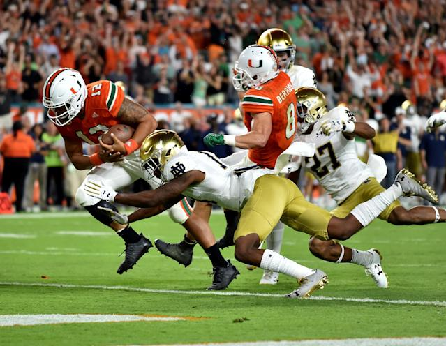 "Nov 11, 2017; Miami Gardens, FL, USA; Miami Hurricanes quarterback <a class=""link rapid-noclick-resp"" href=""/ncaaf/players/240751/"" data-ylk=""slk:Malik Rosier"">Malik Rosier</a> (12) scores a touchdown as <a class=""link rapid-noclick-resp"" href=""/ncaab/teams/nbf/"" data-ylk=""slk:Notre Dame Fighting Irish"">Notre Dame Fighting Irish</a> safety <a class=""link rapid-noclick-resp"" href=""/ncaaf/players/264231/"" data-ylk=""slk:Devin Studstill"">Devin Studstill</a> (14) defends during the first half at Hard Rock Stadium. Mandatory Credit: Steve Mitchell-USA TODAY Sports TPX IMAGES OF THE DAY"