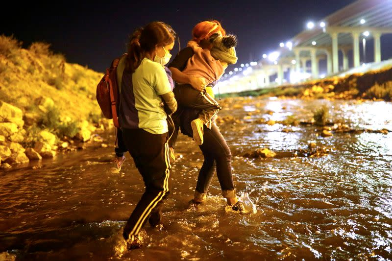 "FILE PHOTO: A mother and her children migrants accompanied a human smuggler or ""coyote"" cross the Rio Bravo river to El Paso, Texas, U.S., as seen from Ciudad Juarez"