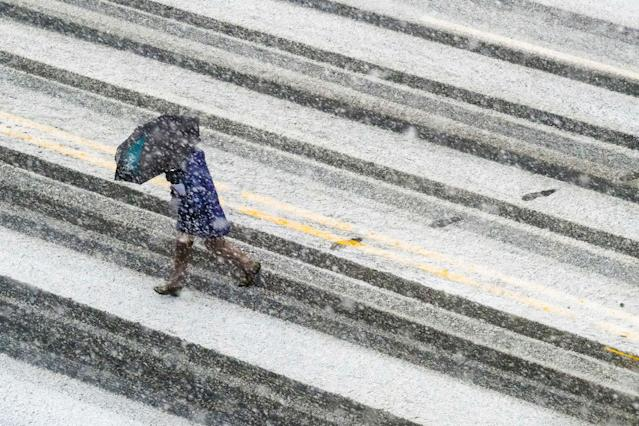 <p>A pedestrian races across the snow covered and tire streaked street in Washington during a spring storm, Wednesday, March 21, 2018. (Photo: J. David Ake/AP) </p>