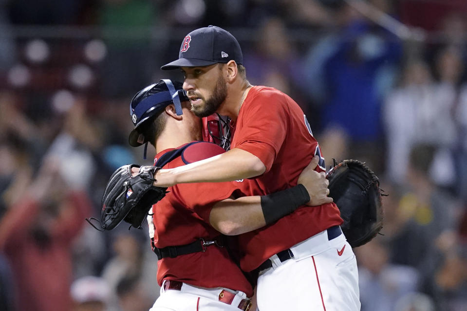 Boston Red Sox closer Matt Barnes, right, hugs catcher Christian Vazquez after the Red Sox's 12-8 victory over the Houston Astros in a baseball game at Fenway Park, Thursday, June 10, 2021, in Boston. (AP Photo/Elise Amendola)