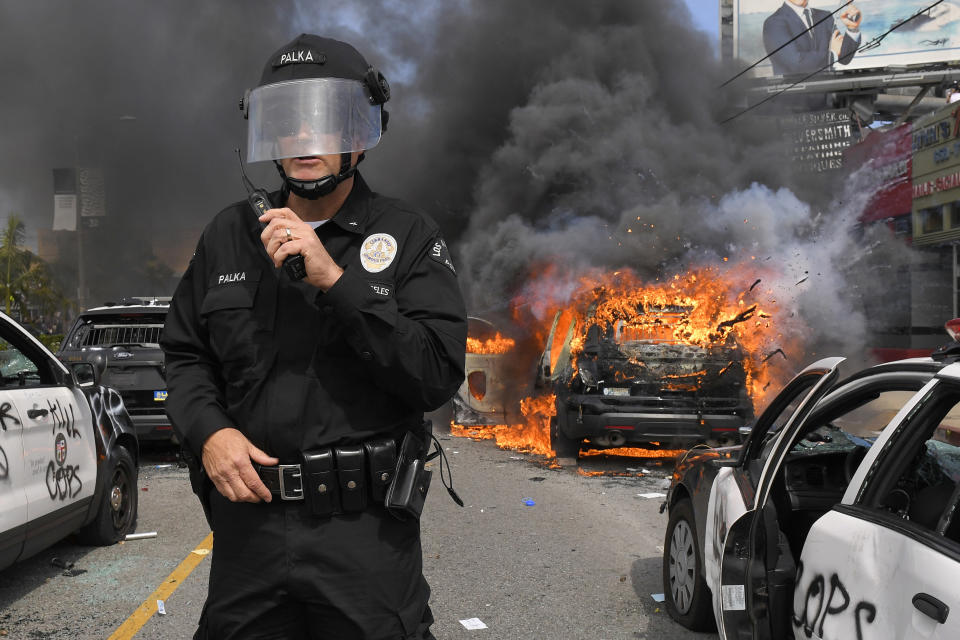 Los Angeles Police Department commander Cory Palka stands among several destroyed police cars as one explodes while on fire during a protest over the death of George Floyd, Saturday, May 30, 2020, in Los Angeles. Floyd died in police custody on Memorial Day in Minneapolis. (AP Photo/Mark J. Terrill)