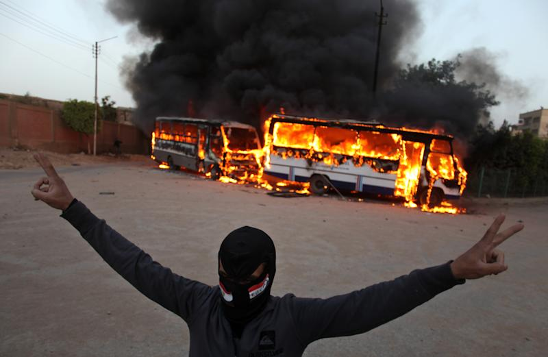 """FILE - In this Friday, March 22, 2013 file photo, a masked protester flashes the victory sign as he stands in front of burning buses during clashes between supporters and opponents of Egypt's powerful Muslim Brotherhood near the Islamist group's headquarters in Cairo, Egypt. Known as the """"Battle of the Mountain,"""" a ferocious recent fight between members of Egypt's Muslim Brotherhood and their opponents in Cairo is looking like a dangerous turning point in the country's political turmoil. Some protesters showed a new willingness to turn to violence against Islamists they accuse of dominating Egypt, while Islamists have heightened their calls for action against opponents they accuse of trying to topple the president. (AP Photo/Khalil Hamra, File)"""