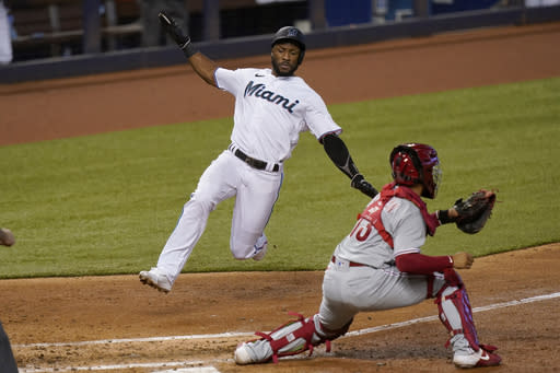 Miami Marlins' Starling Marte, left, scores on a double hit by Jesus Aguilar as Philadelphia Phillies catcher Rafael Marchan waits for the throw during the third inning of a baseball game, Monday, Sept. 14, 2020, in Miami. (AP Photo/Lynne Sladky)