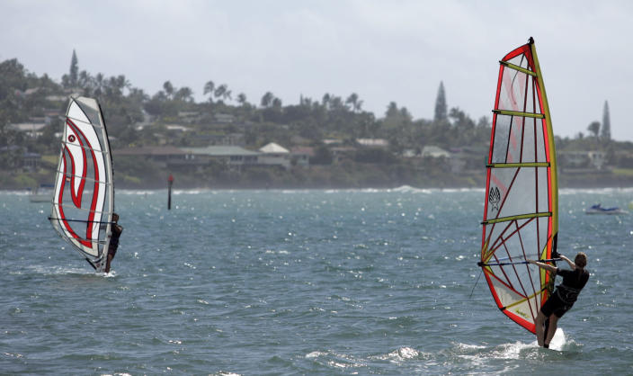 FILE - In this file photo from Thursday, Feb. 1, 2007, two wind surfers sail across the water on Maunalua Bay, in Hawaii Kai, Hawaii. Part of what makes living in Hawaii so pleasant is the gentle breezes. Nowadays, these breezes, called trade winds, are declining, a drop that's slowly changing life across the islands. (AP Photo/Marco Garcia)