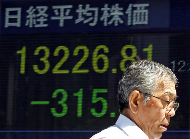 A man walks past the day's Nikkei 225 stock index seen on a board in Tokyo, Japan, Wednesday, Aug. 28, 2013. The growing likelihood of Western military action against Syria pummeled Asian stock markets Wednesday and sent the price of oil soaring. (AP Photo/Shuji Kajiyama)