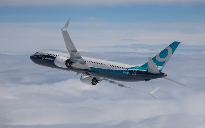 A Boeing 737 MAX 9 flying over clouds