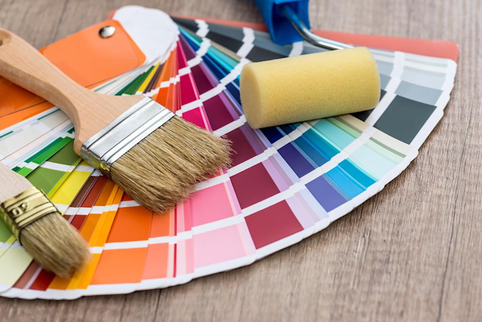 Paint brushes on colour swatch, wooden table background