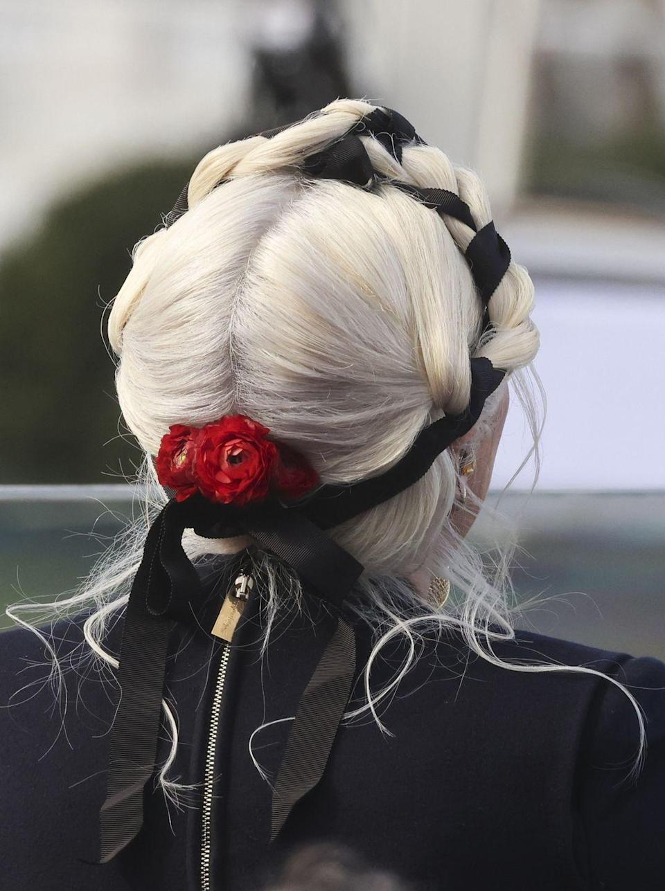 <p>The singer's braids were finished with a cluster of red flowers at the nape of her neck and were, in fact, a second day hairdo that Gaga had previously had styled the day before by go-to stylist Frederic Aspiras.</p>
