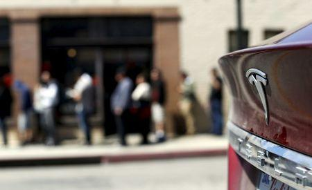 The Tesla logo of a parked vehicle is pictured as people wait in line near a Tesla Motors store to place deposits on the electric car company's mid-priced Model 3 which is expected to cost around $35,000 in Pasadena, California, March 31, 2016. REUTERS/Mario Anzuoni