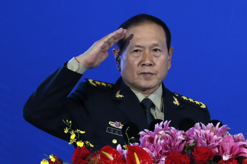 """Chinese Defense Minister Wei Fenghe salutes after delivering his opening speech for the Xiangshan Forum, a gathering of the region's security officials, in Beijing, Monday, Oct. 21, 2019. Wei is issuing a stinging rebuke of the U.S. at a defense forum in Beijing, saying China wasn't fazed by sanctions, pressure and a """"big stick policy."""" (AP Photo/Andy Wong)"""