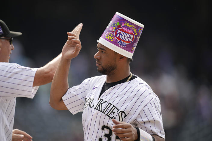 Colorado Rockies catcher Elias Diaz wears a gum container on his head after celebrating with teammates following pinch-hitter Charlie Blackmon's walkoff, RBI-single against the San Diego Padres in the ninth inning of a baseball game Wednesday, June 16, 2021, in Denver. The Rockies won 8-7 to sweep the three-game set. (AP Photo/David Zalubowski)