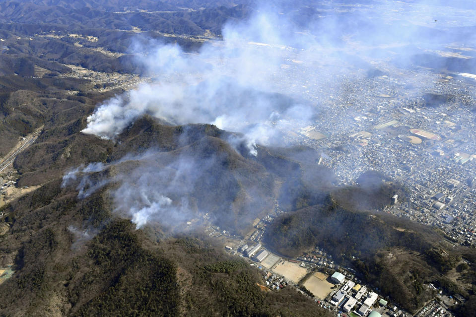 Smoke rises from the site of a wildfire in Ashikaga, Tochigi prefecture, north of Tokyo, Wednesday, Feb. 24, 2021. A forest fire broke out in the rural area Thursday, near another blaze burning since Sunday, Feb. 21. (Kyodo News via AP)